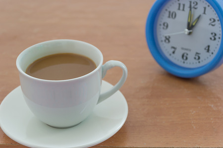 second breakfast: Cup of coffee with Alarm clock on wooden background