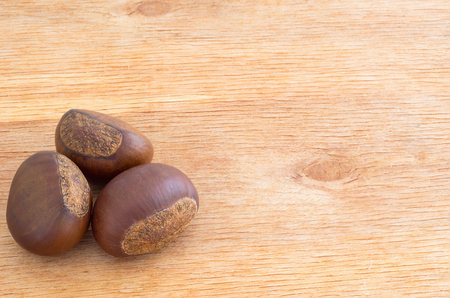 horse chestnut seed: Chestnuts on a brown wooden table Stock Photo