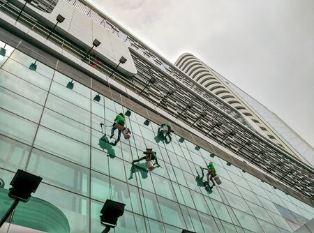 abseiling: the man cleaning wall glass building