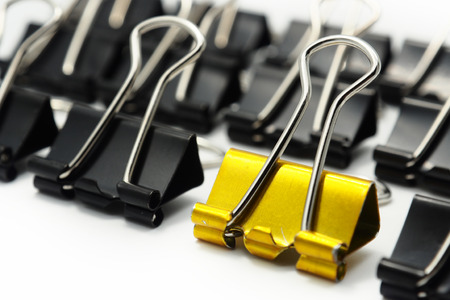 gold PaperClip and black PaperClip white background.leader concept background,The difference,selective focus on gold paperclip