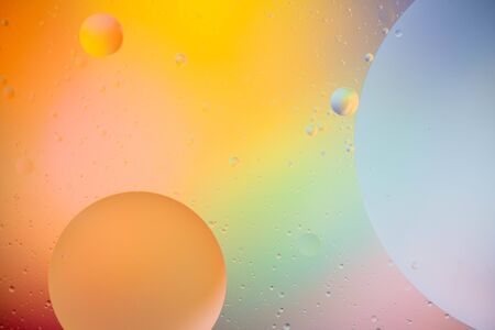 macro of oil mixed with water on colorful gradient background