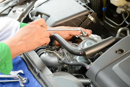 examining: Mechanic examining under hood of car Stock Photo