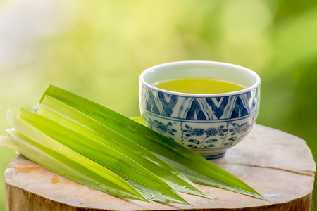 a bowl of pandan juice and pandan leave Stock Photo