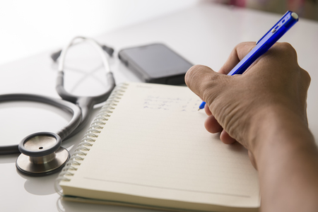 Writing on the medical form with the stethoscope nearby