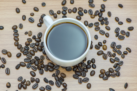 Cup of coffee surrounded coffee beans