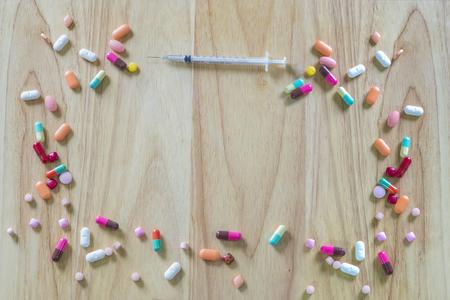 pills and syringe on wood background