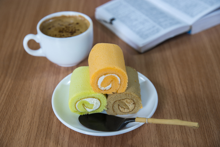 Swiss roll and coffee on a table. Reklamní fotografie