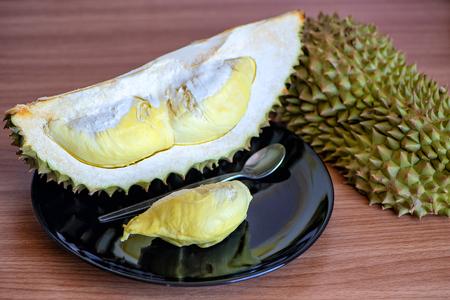 Durian fruit piece on black plate Reklamní fotografie - 105995442