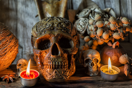 Human skull and candle with on wooden floor and old dirty wall background, and vase flower,and glass,and bottle of wine, still life concep