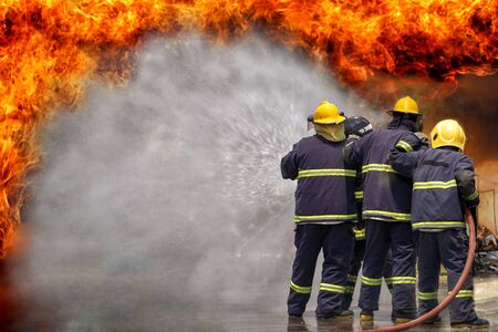 Fireman,fireman using water and extinguisher to fighting with fire flame in an emergency situation., under danger situation all firemen wearing fire fighter suit for safety. Reklamní fotografie - 128587506