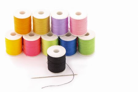 Multi-colored thread sewing and needle clothing repair concept.