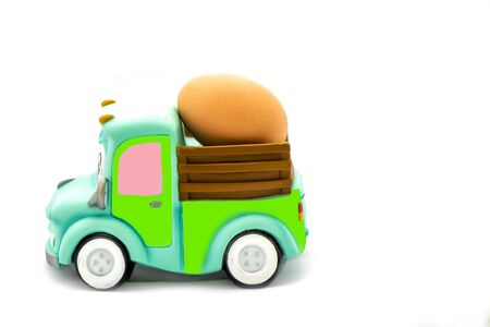 Car toy carrying egg Easter concept background.