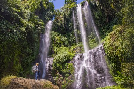 Young man with straw hat relaxes looking at the Sekumpul waterfalls in jungles on Bali island, Indonesia
