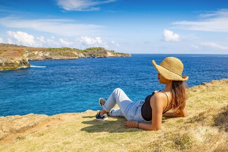 Young woman to relaxed at Broken Beach, located in Nusa Penida Island, the southeast island of Bali, Indonesia. The amazing tourist attraction of the rock  S 版權商用圖片