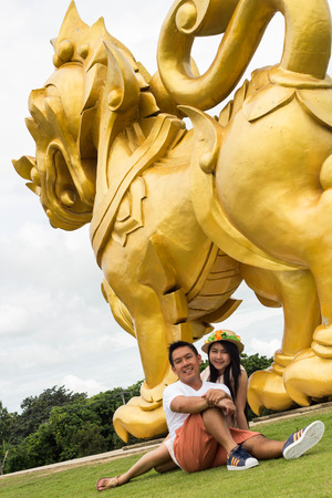 Couple posing with statues of lions photo