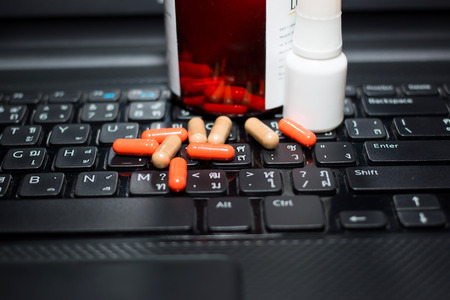 many pills and computer keyboard
