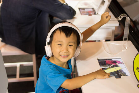 Asian kid play computer internet games and wear headset to communicate photo
