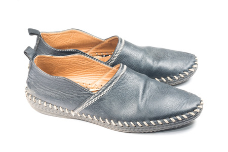 informal clothing: old black shoes on white background