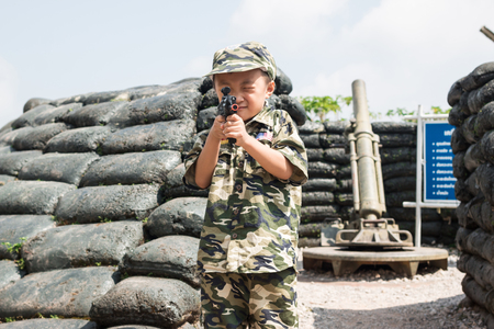 barracks: Young boy dressed like a soldier with a gun in barracks Stock Photo