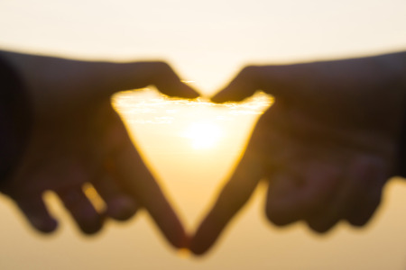 kink: Hands in shape of Heart around sunset