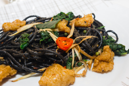 Black spaghetti with prawns on white plate