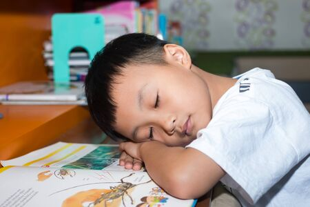 little boy reading book in the library Stock Photo