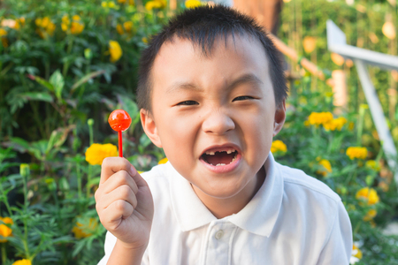 Asian boy eating candy until dental caries