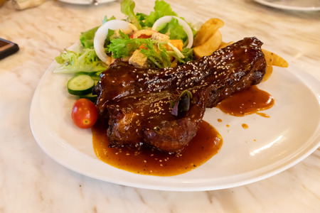 Pork ribs Sprinkle with sesame seeds Topped with red sauce