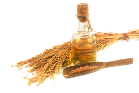 Bottle of rice bran oil and ear of rice isolate on white background