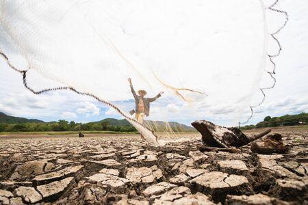 I pescatori lanciano una rete ma non possono pescare a causa della siccità. a Terreno con terreno secco e screpolato a causa dell'aridità del riscaldamento globale