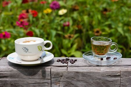 Hot coffee and Tea in a glass On the timber In the flower garden