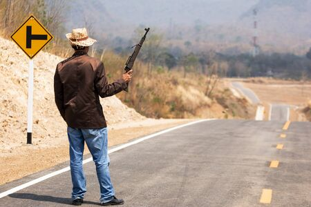 cowboy with a gun on beautiful road in the countryside Of Thailand Through beautiful mountains Banco de Imagens