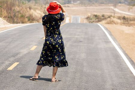 Beautiful women are waiting for the bus on beautiful road in the countryside Of Thailand Through beautiful mountains Banco de Imagens