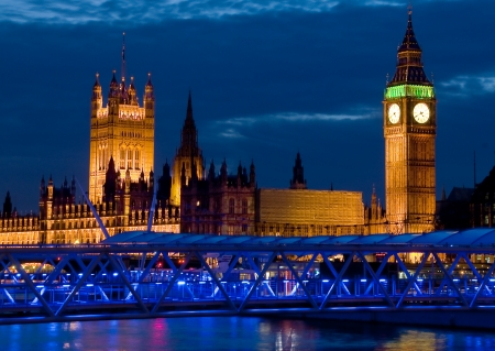 Big Ben and house of Parliament in London at dusk with a blue illuminated pier in the foreground  Stock Photo