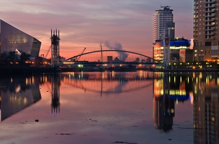 A beautiful pink sky at the Salford Quays picturing Millennium Bridge, Imperial War Museum and Lowry Foto de archivo