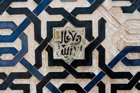 andalusian: Islamic text engraved on a wall surrounding by a beautiful moorish pattern in ceramic  Stock Photo
