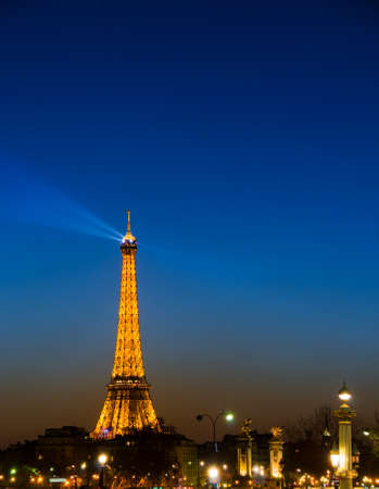 Eiffel tower paris at night with search light beaming through blue sky