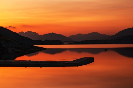 loch: Loch Leven in highlands of Scotland near Glencoe  A beautiful sunset with a pier in the foreground and Scottish mountains in the background