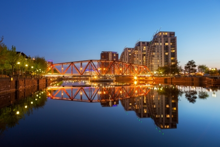 Reflection of red iron bridge and modern building in the clear water of Manchester canal Standard-Bild