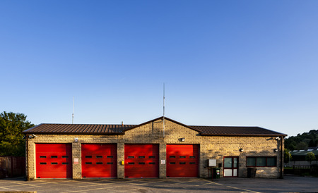 building on fire: Old firestation near Hudderfield in Yorkshire England. Red doors and blue sky show a good contrast between colors.
