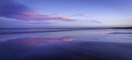 Peaceful and serene scene of beach with clouds lit by last light of the day at Hartlepool beach England.
