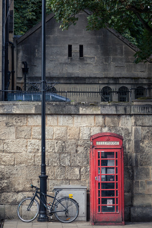 phone booth: Red phone booth an iconic symbol of british heritage and an old bicyle on the streets of oxford England. Editorial