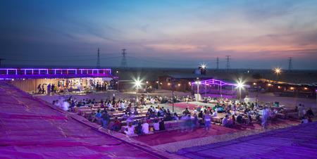 Kamp in het midden van de woestijn mensen genieten van eten en dans in Dubai, UAE.