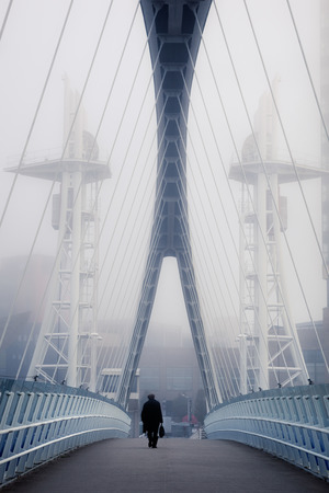 millennium: Man crossing the bridge going for a work in a foggy morning.