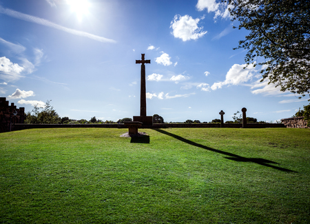 Silhouette of a cross against a blue sky and its shadow on green grass. photo