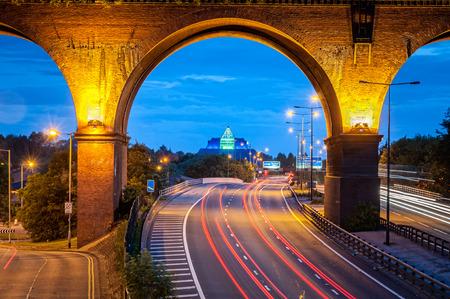 Spoorwegviaduct oversteken snelweg M60 in de buurt van Manchester, UK. Achterlichten van de auto's verlaten spoor onder de brug.