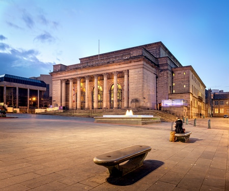 Sheffield city hall building illuminated at night. A woman waiting alone on bench with her luggage.