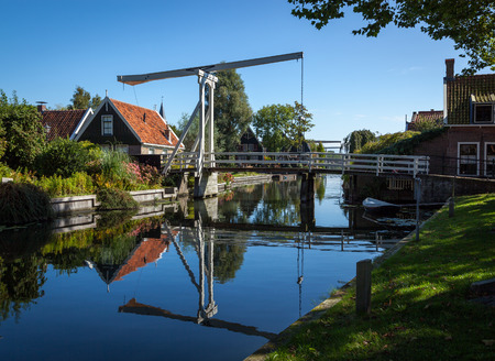 marken: Traditional rural setting of a small village in Holland, Netherlands. Suspension foot bridge crossing over teh river.