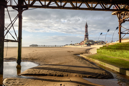 enhancing: View of Blackpool Tower through the frame of and old pier. A golden evening light enhancing color of yellow sand of beach.