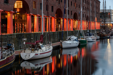 dockside: Boats are moored in front of the old warehouse pillars at Albert docks, Liverpool, UK.